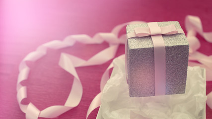 Banner Festive composition with gift box on a bright pink background.