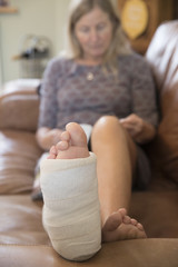 Close Up Of Mature Woman With Leg In Plaster Cast Lying On Sofa At Home