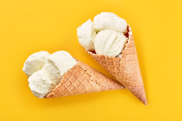 ice cream balls in a Waffle Cone on a yellow Background. Vanilla ice cream in a waffle cone.