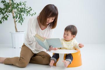 赤ちゃんに本を読む女性