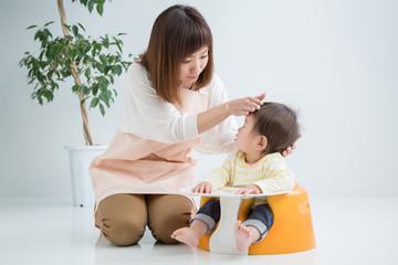 赤ちゃんの熱を測るエプロン姿の女性
