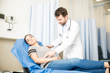 Doctor checking woman with stomach ache