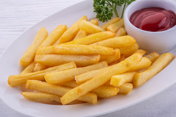 French fries fried in oil with salt, spicy ketchup in a white plate