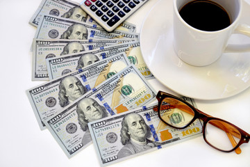 Cash money, US dollars, spread out on table with coffee cup, eye glasses and calculator.