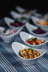 Salads in white plates on the table. Salad with meat, potatoes and carrots in the foreground. In the blurry background, there are other different salads.