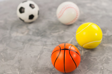 Four new soft rubber basketball and baseball and tennis and soccer balls on old worn cement
