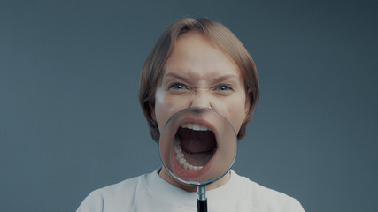portrait of caucasian wooman with magnifier makes fun faces. Magnifier to the mouth Shout screaming mouth