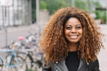 Curly woman smiling in the street