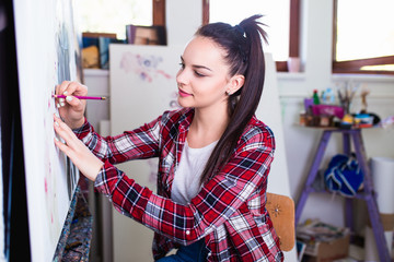 Beautiful female artist working on painting in her studio.