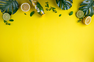 Monstera leaves and bottle tropical water on yellow background. Detox fruit infused water, citrus fruits and mint leaves. Top view, flat lay, copy space