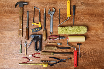 Tools for repair: a hammer, drills, pliers, platens, screwdrivers, glass cutters, staplers on a wooden background