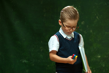 Funny little boy in shirt and vest - an elementary school student holding lot of colored felt-tip pens on dark green background.