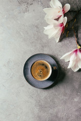 Blue cup of black espresso coffee and spring flowers magnolia branches over grey texture background. Top view, space. Spring greeting card,