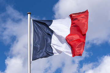 French Flag waving against blue Sky during sunny Day in France