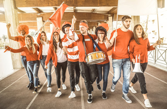 Football supporter fans friends cheering and walking to soccer cup match at intenational stadium - Young people group with red and white t-shirts having excited fun on sport world championship concept