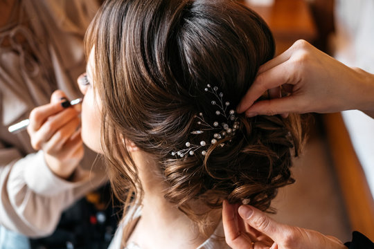 A hair stylist and make-up artist prepare a bride for the wedding day