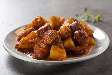 Potatoes stew with pork sausage slices and tomato sauce