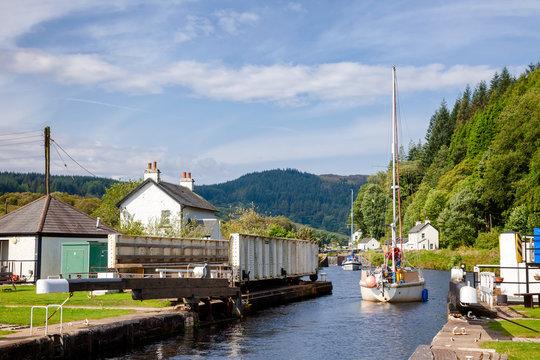 Boat passes Cairnbaan swing bridge and lock at Crinan Canal Kintyre peninsula Argyll and Bute Scotland UK