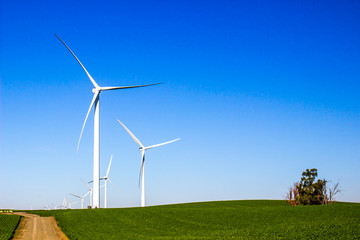 Energy Making Windmills On Hillside In Open Field