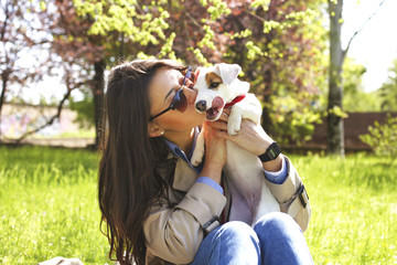 Attractive hipster young woman in sunglasses kissing jack russell terrier puppy in park, green lawn & foliage background. Funny purebred dog kissed by her female owner. Portrait, close up, copy space.