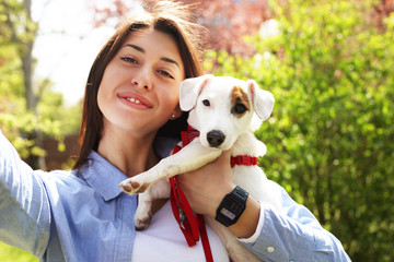 Beautiful young woman takes selfie with her cute jack russell terrier puppy on picnic in park, green grass & foliage background. Female owner & small pet, purebred funny dog. Close up, copy space
