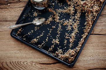 Baking tray with freshly baked homemade granola. Healthy vegan snack easily prepared at home. View from above, wooden table background.