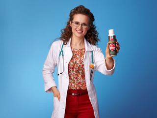 smiling pediatrist woman showing insect repellent on blue