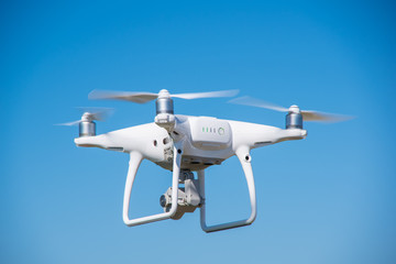 The modern drone, quadrocopter is in the air against the background of the sky and grass