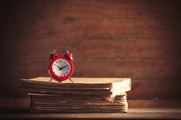 Little alarm clock and books on wooden background. image in old color style