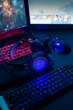 Laptop, computer, keyboard, mouse, headphones accessories for the gamer on the background of the monitor with the game, the workflow