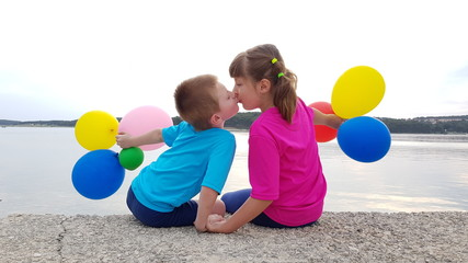 Fratello e sorella giocano con dei palloncini colorati e si scambiano un bacio