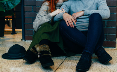 the couple is sitting on the floor in an embrace. embrace. a female hand with a ring, a man's hand with a watch. talking. gray sweaters.