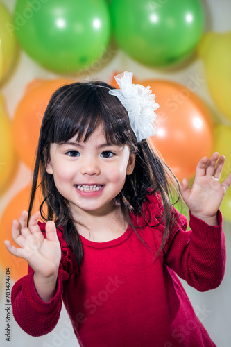 Happy 3 Year Old Girl In Front Of Birthday Balloons Studio Shot