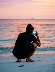 Junger Mann macht Foto am Strand im Sonnenuntergang