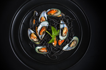 Black spaghetti. Black seafood pasta with mussels over black background. Mediterranean delicacy food.