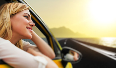 Travel or vacation. Beautiful blond girl in car on the road to the sea at sunset.