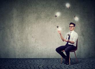 Man juggling with glowing light bulbs