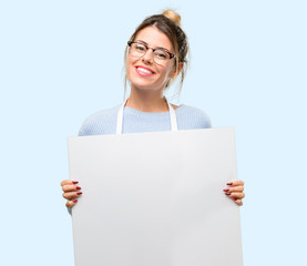 Young woman shop owner, wearing apron holding blank advertising banner, good poster for ad, offer or announcement, big paper billboard