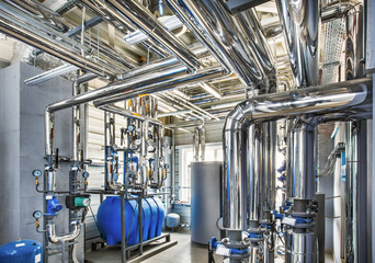 The interior of an industrial boiler house with a multitude of pipes, barrels and sensors