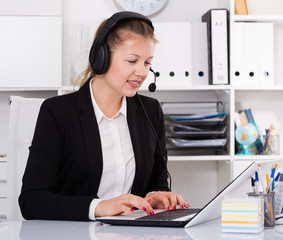 Young woman in black suit is talking by headset with client
