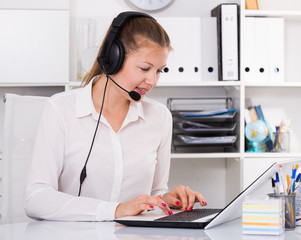 Female is working at a computer and talking by headset with client
