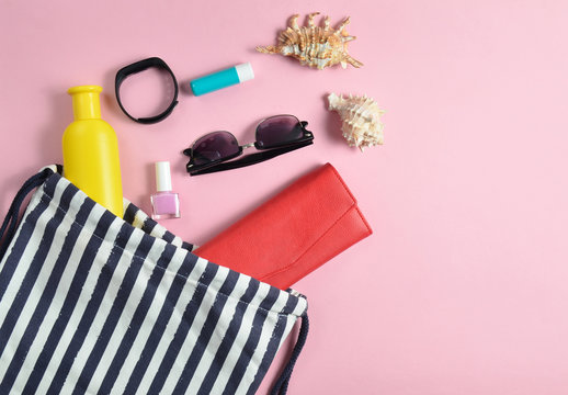 Beach bag and accessories for relaxing on the beach layout on pink pastel background. The concept of the resort at sea, summer time. Top view, flat lay, minimalism.