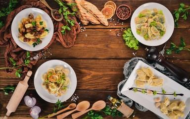 Set of Ukrainian cuisine. Vareniks, fresh vegetables, spices. Top view. On a wooden background. Copy space.