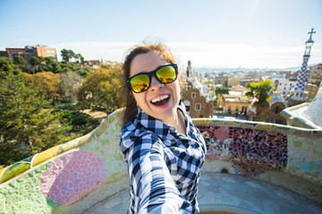 Young happy woman making selfie portrait with smartphone in Park Guell, Barcelona, Spain. Beautiful girl looking at camera taking photo with smart phone smiling