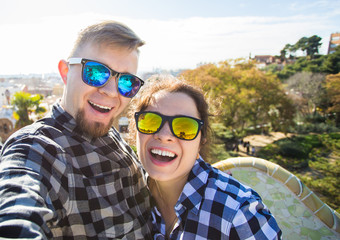 Travel couple happy making selfie portrait with smartphone in Park Guell, Barcelona, Spain. Beautiful young couple looking at camera taking photo with smart phone smiling in love