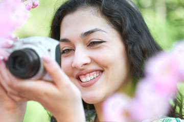 girl with camera taking pictures of pink flowers, face closeup