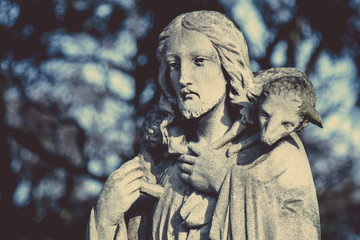 Ancient statue of Jesus Christ is the Good Shepherd with the lost sheep on his shoulders. (Biblical tradition, religion, Christianity, God, faith concept)