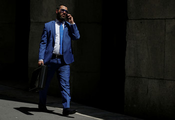 A man in a suit talks on his phone as he walks on Wall Street during a warm spring day in New York City