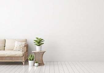 Home interior mock up with wicker rattan sofa, beige pillows, table, and green plants in living room with empty white wall. 3D rendering.