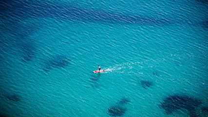 Aerial view of people padding on SUP (stand up paddle) on crystal clear blue sea with rocks under water. Unidentifiable people paddle boarding.